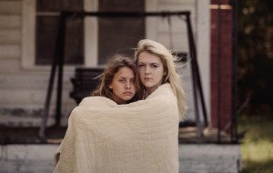 Two beautiful sad teenage girls embracing with quilt outdoors
