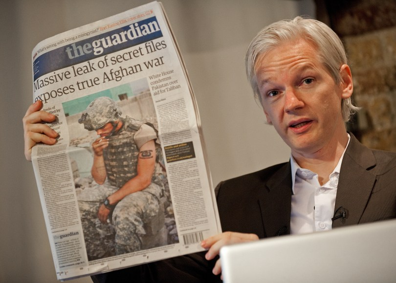 Julian Assange, leader of WikiLeaks, holds up a copy of the Guardian with a front page article that used leaked Pentagon data. Leon Neal/AFP/Getty