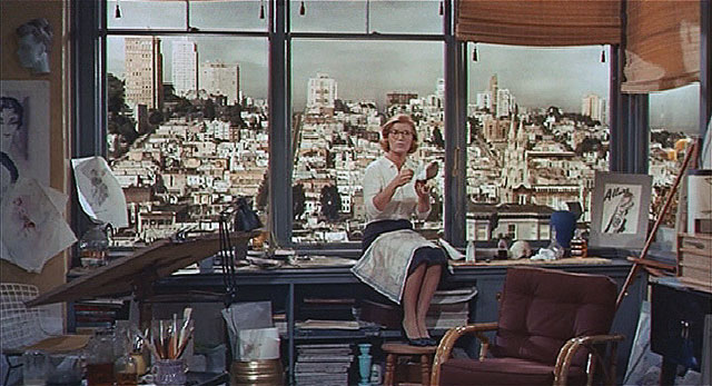 """""""Scotty visits his old flame Midge (Barbara Bel Geddes).  The vista from her apartment window looks west to Russian Hill from the top of Union Street on Telegraph Hill.  The building on the skyline to the left of Midge's shoulder is the La Mirada apartment building at 1100 Union Street.  This scene was filmed in a studio using a photograph to virtually set the location."""" (Courtesy Reel SF)"""