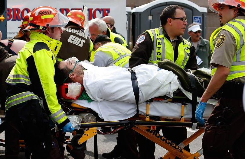 A man is loaded into an ambulance after he was injured by one of two bombs exploded during the 117th Boston Marathon. (Jim Rogash/Getty Images)