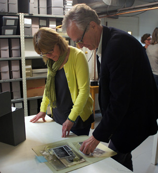 Alison Moore and Jon Christensen look through photos in the vault of the California Historical Society. (Photo: Lauren Sommer/KQED)
