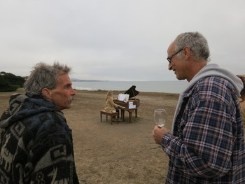 Neighbors and tourists gather around the old pianos that Artist Mauro Fortissimo hauled out to the beaches of San Mateo County. (Francesca Segrѐ/ KQED)
