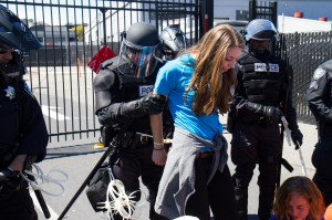Richmond police arrest a demonstrator at the gates of Chevron's refinery complex during an Aug. 3, 2013, protest against the company's environmental practices and to mark the one-year anniversary of a massive fire at the facility. (John Orvis/johnorvis.com