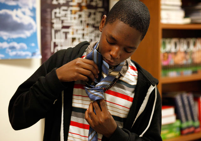 Nequwan Taylor practices tying a tie during a June session of the 10th grade manhood development class at Oakland High School. (Lacy Atkins/San Francisco Chronicle)