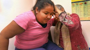 Dr. Razia Sheikh, a Fresno pediatrician, examines 12-year-old Veronica Regalado, who is struggling with a weight problem. (Joel Pickford/Center for Investigative Reporting)