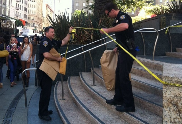 Police officers remove a suspicious package that led to the evacuation of San Francisco's Union Square at midday.