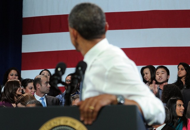 A man (in background, second from right) heckles President Obama as he addressed an audience at San Francisco's Betty Ann Ong Chinese Recreation Center on the topic of immigration reform. (Jewel Samad/Getty Images)