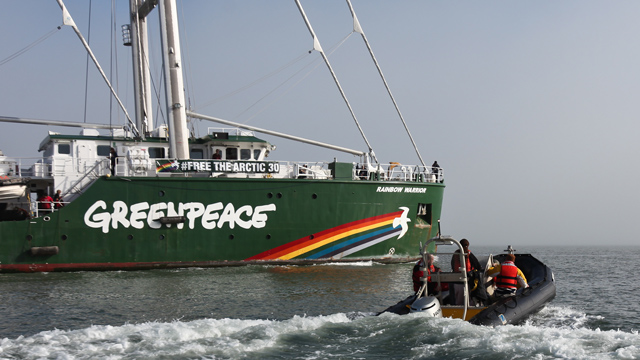 Greenpeace members motor out in a small boat to greet the Rainbow Warrior III as it enters a foggy San Francisco Bay on Friday. (Deborah Svoboda/KQED)