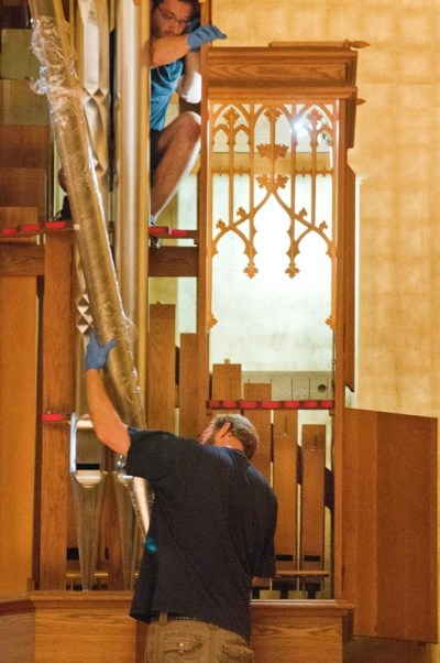 """Workers install the Noack organ's """"dutch metal"""" gold leaf walls; and load-in organ parts for assembly on July 29, 2013."""