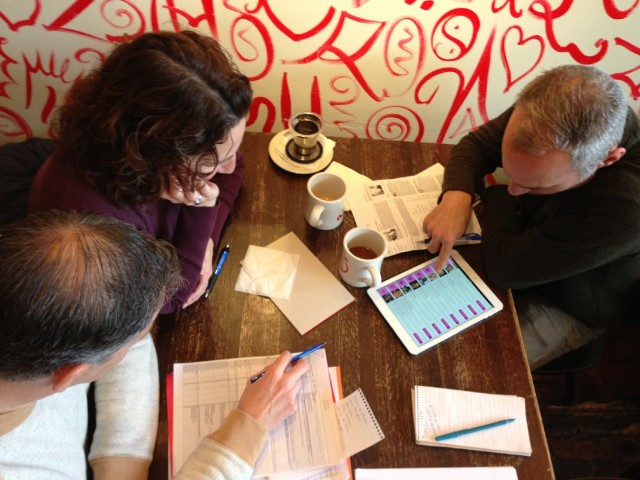 Contestants Joel (left) and Jamie (right) join teammate Lisa at Ritual Café in San Francisco as they huddle over spreadsheets and data before making their 2014 Dead Pool picks. (Scott Shafer/KQED)