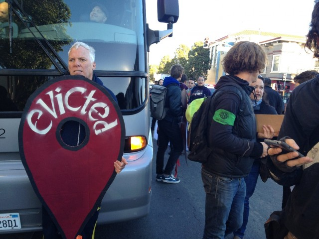 Anti-eviction protesters block a Silicon Valley bus -- this one carrying Apple employees -- at 24th and Valencia streets in San Francisco's Mission District (Vinnee Tong/KQED)
