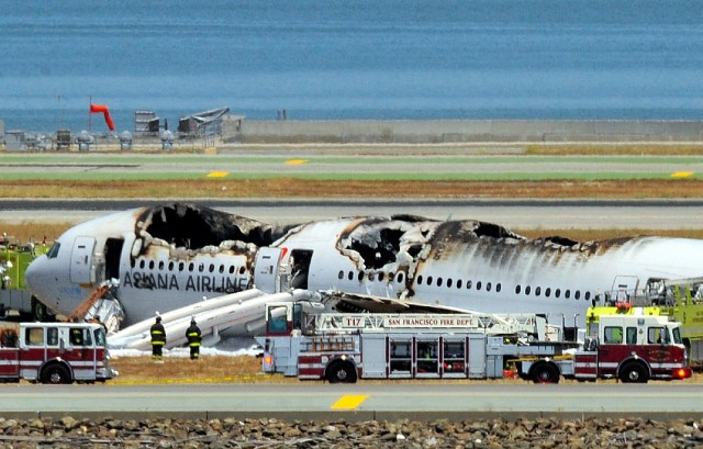 Fire trucks surround an Asiana Airlines Boeing 777 on the runway at San Francisco International Airport after it crashed last July. (Josh Edelson/AFP/Getty Images)