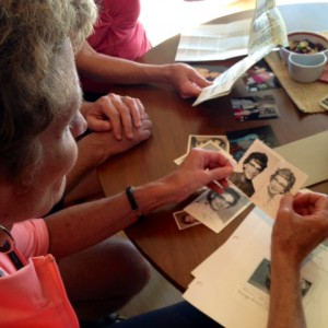 Elsie Fossum's nieces and nephews look at family photos of their aunt, on the seventh anniversary of her death. (Mina Kim/KQED)