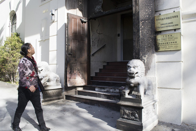 Xue Kui Zhang, who moved to San Francisco from China in 2008, walks past the entrance of the Chinese Consulate, which is charred after a suspected arson incident last night. (Sara Bloomberg/KQED)