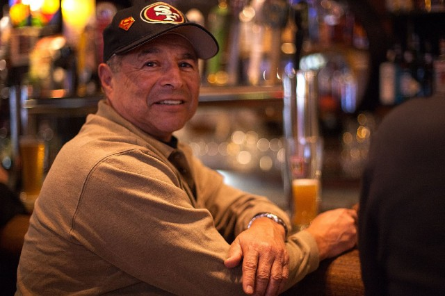 "Art Olivares was sitting at a barstool at Lefty O'Douls when we approached him. His first memory of the 49ers was a dark one: a 49ers' playoff loss to the Dallas Cowboys (they knocked the Niners out of the postseason in 1970. '71 and '72). But he expects this season to end differently. ""The expectations are the same: They won last year, and they're going to win this year."" (Mark Andrew Boyer/KQED)"