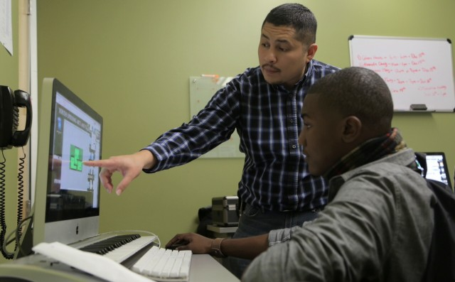 Darius Reed is learning from Arturo Arechiga how to animate characters for the team's video game—Mr. Platformer.