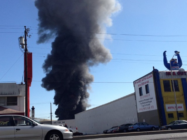 A fire in a taxicab garage in San Francisco's Bayview neighborhood sent an attention-getting plume of black smoke into the air at midday Monday. (Francesca Segre/KQED)