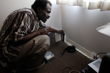 Eddie Williams, 62,  glues items such as video cassettes to his walls to stop mice from getting into his Nevin Plaza apartment. Williams, whose rent is $251 a month, asked the Richmond Housing Authority to fix the problem, but he says nothing happened.(Lacy Atkins/San Francisco Chronicle)