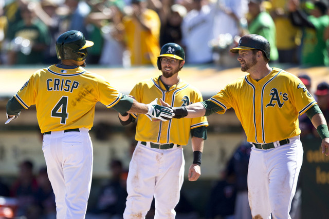 Coco Crisp is congratulated by Eric Sogard, center, and Stephen Vogt after hitting a three-run homer in the Oakland A's division-clinching win against the Minnesota Twins last September. (Jason O. Watson/Getty Images)