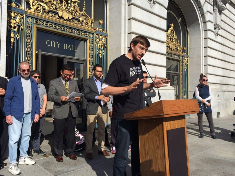 Tenants call on city officials to boost funding for eviction defense. At podium: Tyler McMillan, executive director of the Eviction Defense Collaborative. (Bryan Goebel/KQED)