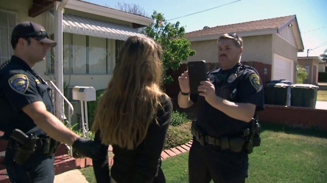 Officer Rob Halverson of the Chula Vista police verifies the identity of a woman just arrest for possession of narcotics with facial recognition software. (Center for Investigative Reporting)