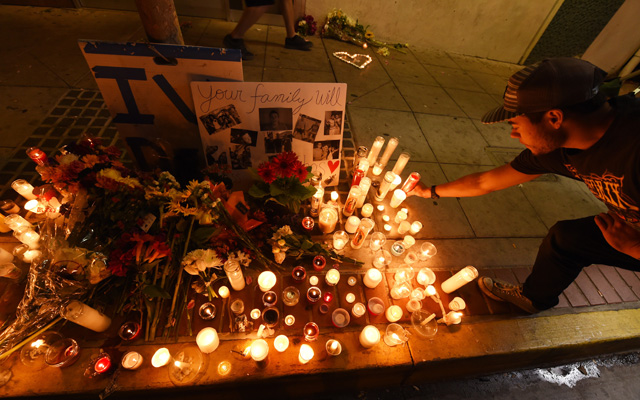 A student lights a candle at a memorial for one of the victims of Elliot Rodger during a series of attacks near the UC Santa Barbara campus. (Robyn Beck/AFP-Getty Images)