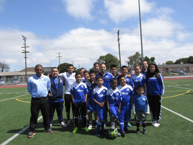 President of the Richmond Sol Soccer League Diego Garcia in the middle with a mix of players from the recreational and competitive teams. (Cristina Matamoros/KQED)