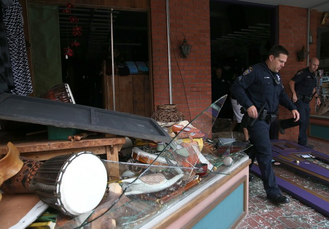Police officers exit a damaged building. (Justin Sullivan/Getty Images)