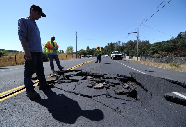 Nicholas George looks under a buckled highway just outside of Napa, California. (Josh Edelson/AFP/Getty Images)