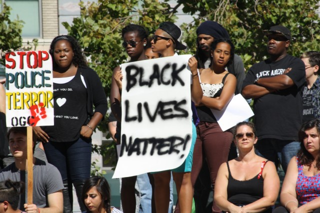 People gather at Oakland City Hall Aug. 14 and hold a moment of silence for people killed by police five days after the fatal shooting of Michael Brown in Ferguson, Missouri. (Alex Emslie/KQED)