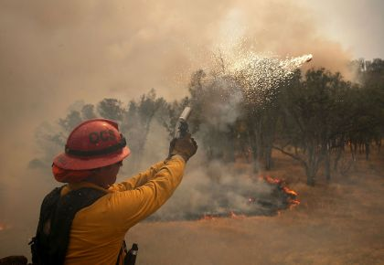 Oceanside Fire Department Capt. Greg DeAvila shoots a flare into dry brush during a burn operation to head off the Rocky Fire on Sunday, east of the town of Clearlake. The tactic is meant to starve advancing fires of fuel. By Monday, 3,000 firefighters were battling the blaze, the state's biggest so far this year.