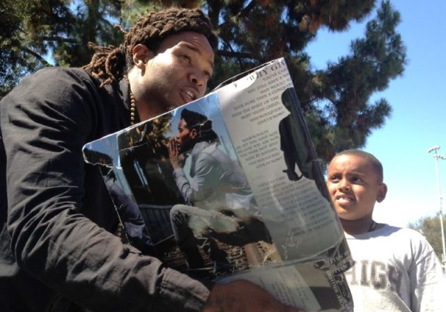 Compton poet Robert Williams aka Young Robb unleashes some of his socially conscious rhymes for some kids at the Watts Summer Festival