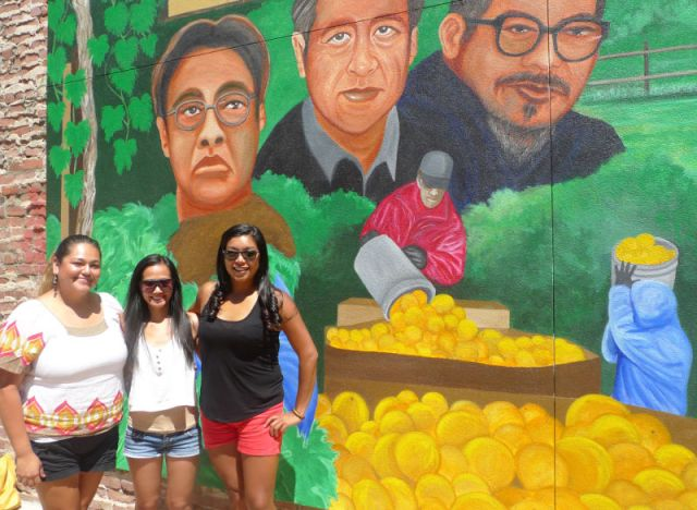 Angelica Perez, Melanie Retuda and Larissa Portillo (L-R) in front of a recently-completed mural in downtown Delano featuring Philip Vera Cruz, Cesar Chavez and Larry Itliong.