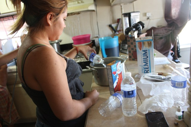 Medina's daughter Guadalupe prepares for dinner, pouring bottles of water into a pot to make macaroni and cheese.