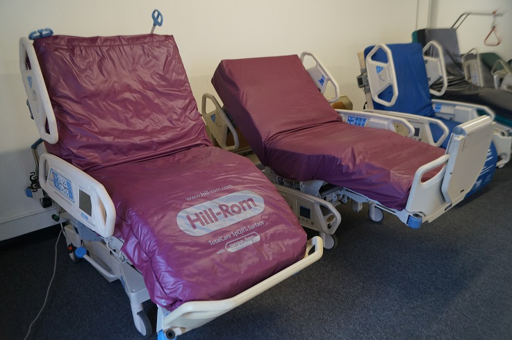 Refurbished Hill Rom P1900 Totalcare Sport 2 (left) next to a Hill Rom P1900 Sport 1 hospital bed