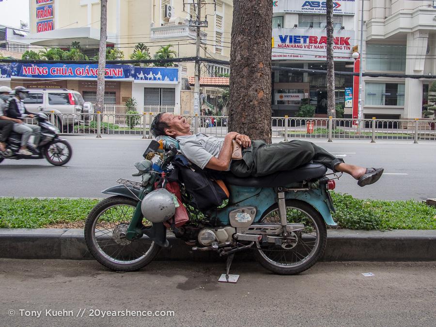 Man sleeping on motorbike in Saigon