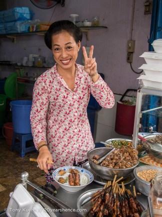 Smiling Vietnamese woman serves food