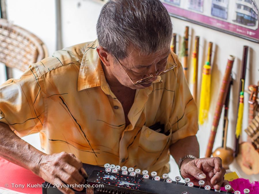 Man plays an old instrument, Georgetown, Penang, Malaysia