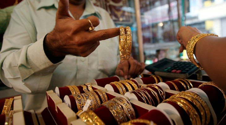 A shopkeeper shows gold bangles to a prospective buyer at a jewellery shop in Mumbai October 8, 2009. India gold demand stayed weak on Thursday as record international prices kept traders at bay in the middle of the festive season, dealers said. REUTERS/Arko Datta (INDIA) - RTXPFIR