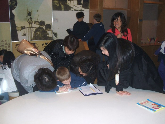 The author's son surrounded by a group of Chinese women crowded very closely around him as he bends over a book.