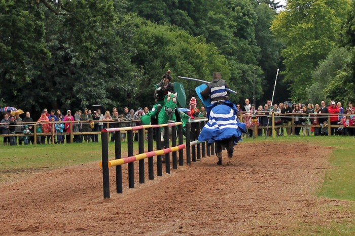 Riders in medieval costume face off in a jousting match
