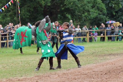 Actors in medieval costume stage a swordfight