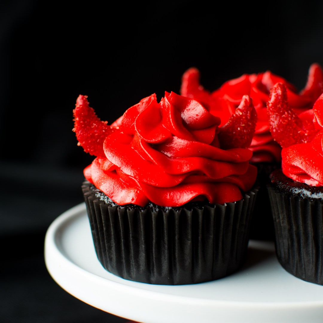 Super moist and intensely dark chocolate devil's food cupcakes with a kick of cinnamon, chili powder, and cayenne, topped with a red velvet buttercream and darling little devil horns!