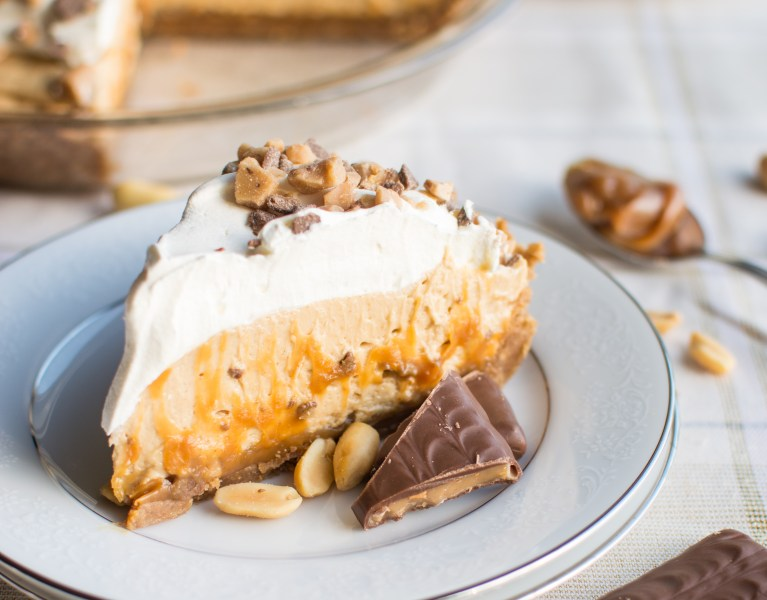 A crisp graham cracker toffee crust filled with rich caramel, bits of toffee, fluffy peanut butter cream filling, and topped with whipped cream and even more toffee bits!
