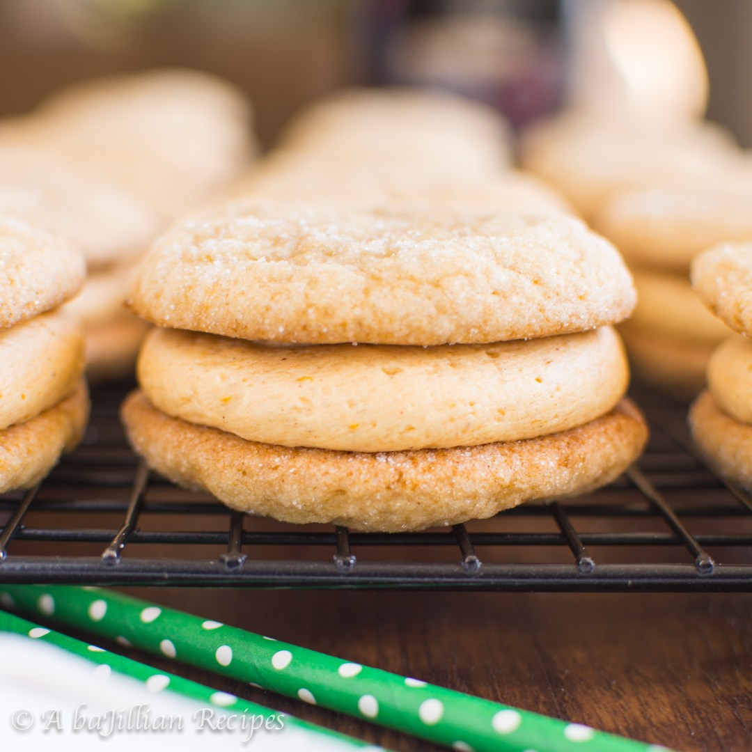 Soft and chewy sugar cookies infused with the warm sweetness of maple syrup, filled with a cloud of fluffy pumpkin buttercream frosting!