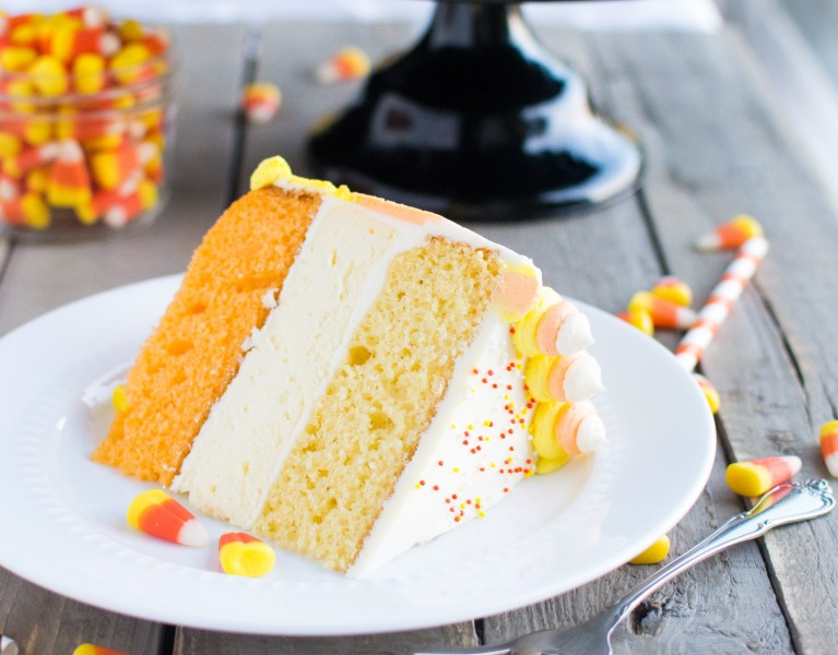 A fun and festive cake made with layers of fluffy cake and a rich and creamy layer of cheesecake, brilliantly frosted in candy corn colors!