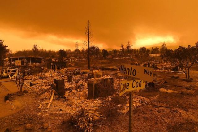 The sky glows orange above burnt out homes