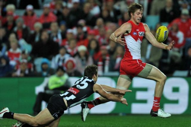 Sydney Swans' Alex Johnson juggles the ball ahead of Collingwood's Jamie Elliott