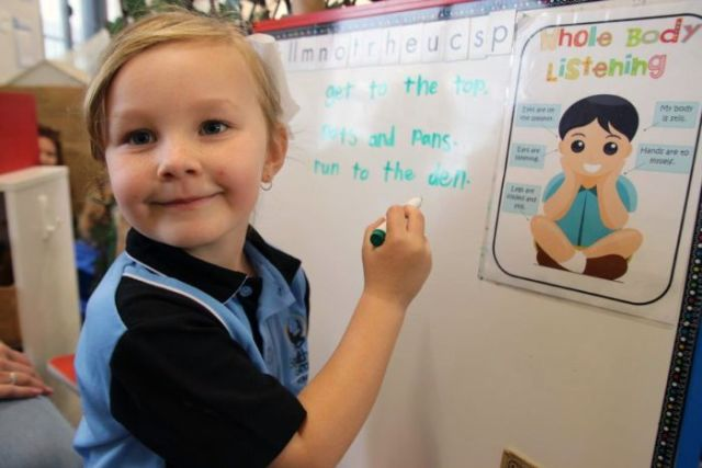 A young school student draws on a whiteboard.