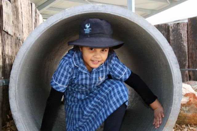 A student is crouched down in a large cement cylinder in the playground.
